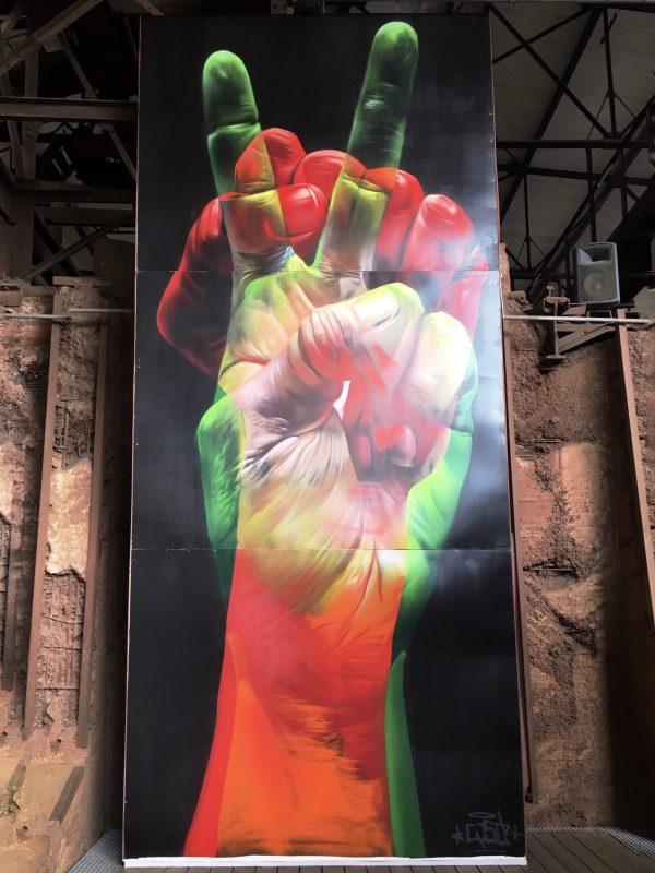 Eine Hand in grün zeigt das Peace-Zeichen wird überlagert von einer Hand in rot die die Faus ballt.