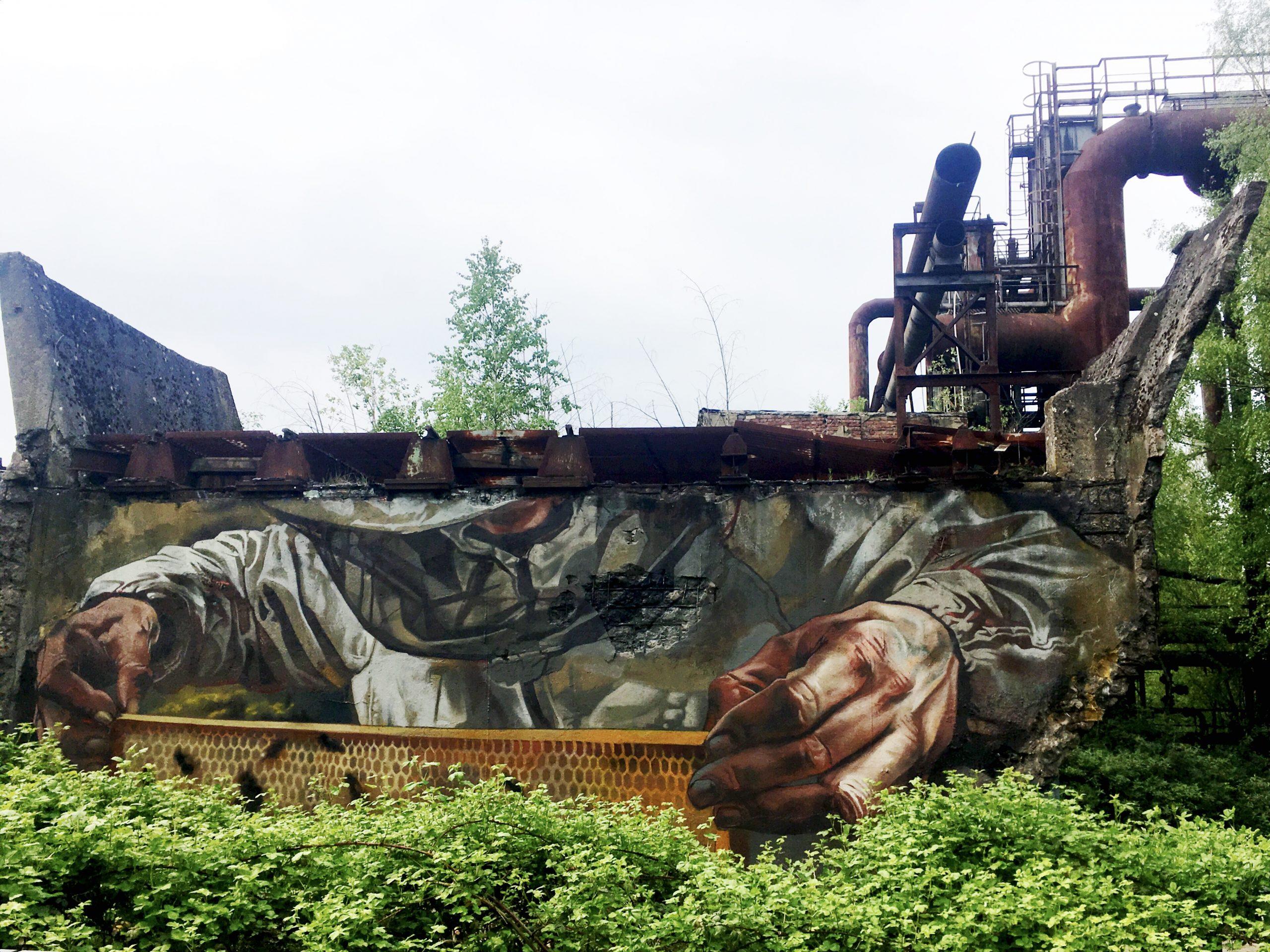 Mural eines Imkers auf Betonwand. Im Vordergrund Buschwerk